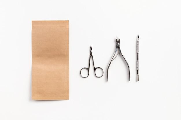 흰색 테이블에 종이 봉지와 매니큐어 도구. 악기 건강 관리 개념의 살균