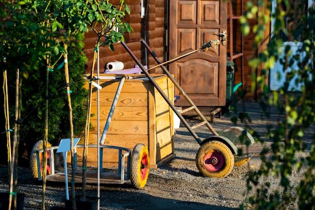 영토의 조경 설계를위한 도구 인 헛간 근처에서 접힌 정원에서 일하는 도구
