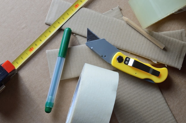 段ボールのスクラップと一緒にテーブルに配置された段ボールを操作するためのツール。