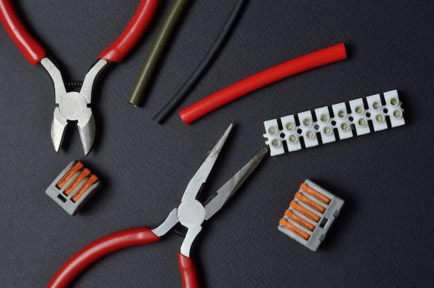 電気、端子台、熱収縮管を操作するためのツールは、暗い背景にあります。