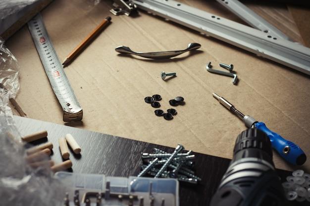 Инструменты, мебельные детали, упаковочная пленка, шурупы на листе картона. сборка мебели вручную, мебель для самостоятельной сборки