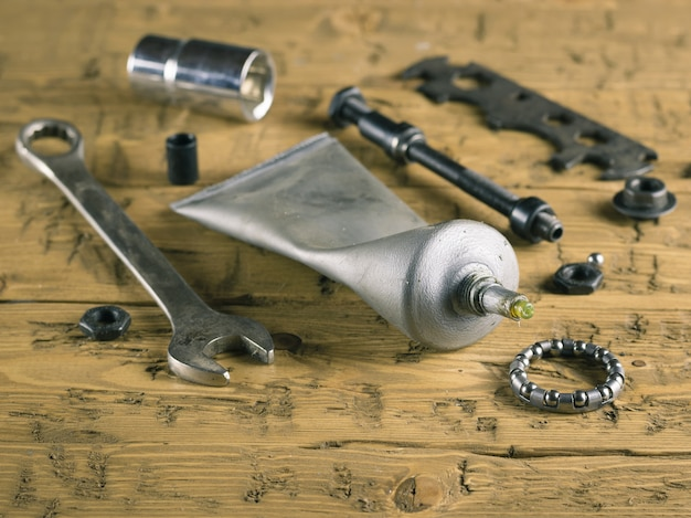 Tools and grease for bike repair on the wooden table.
