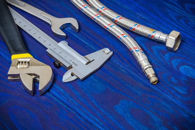 Tools and hose for plumbers on wooden blue boards
