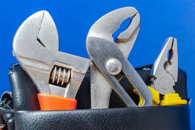 Инструменты в кожаной сумке на синем фоне для ремонта - гаечные ключи и плоскогубцы.