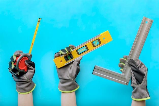 손에 도구입니다. 손에는 파란색 배경에 건설 및 목공 도구가 있습니다. 배너, 콜라주, 건설 및 목공 개념입니다.