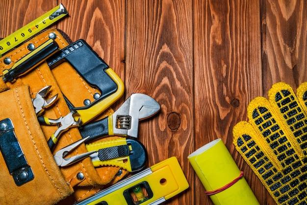 Инструменты в сумке для мастера-строителя, подготовленные перед работой на коричневых деревянных досках