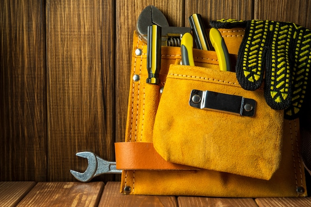 Tools and instruments in leather bag isolated on wooden board