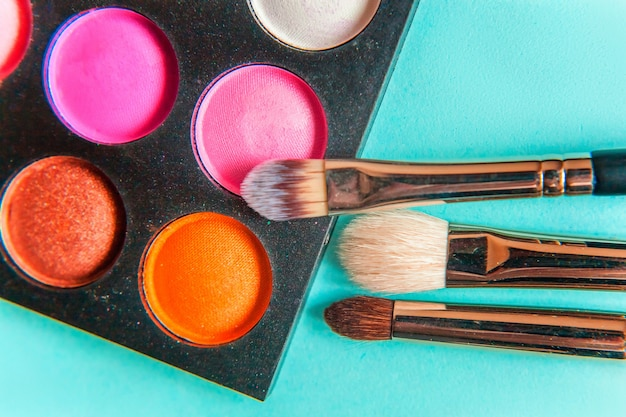 Tools for makeup and cosmetics different shades of eyeshadow palette and make up brush on trendy colorful blue pastel