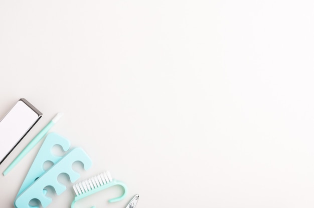 Tools for manicure and pedicure at home in blue on a white background. professional care of women's nails with tweezers, a file and a brush. minimalistic copy space backdrop.