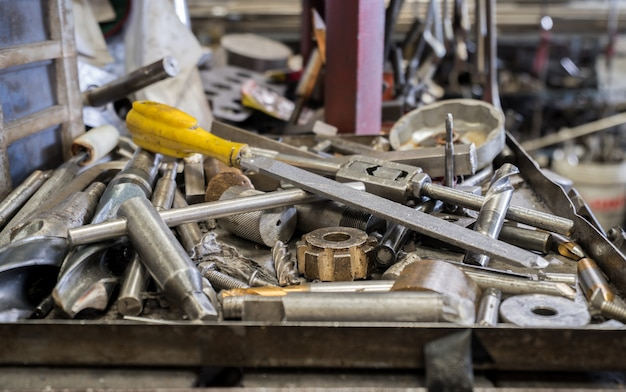 Tools on metal tray with untidy tools at background