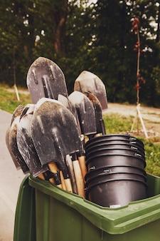 나무의 어린 묘목을 심기 위한 인간 노동 삽과 양동이 도구. 도시의 젠트리피케이션을 위한 배경. 조경, 자연, 환경 및 생태학의 개념. 복사 공간