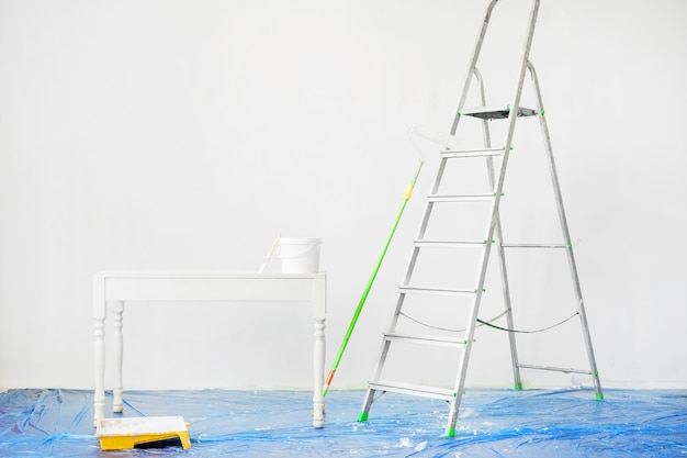 Tools for painting walls: a stepladder, roller, tray, bucket of paint, a brush on the floor with a protective film. preparation for painting the walls.