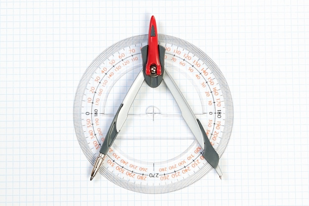 Tools for plotting compass and protractor. on a white wall.