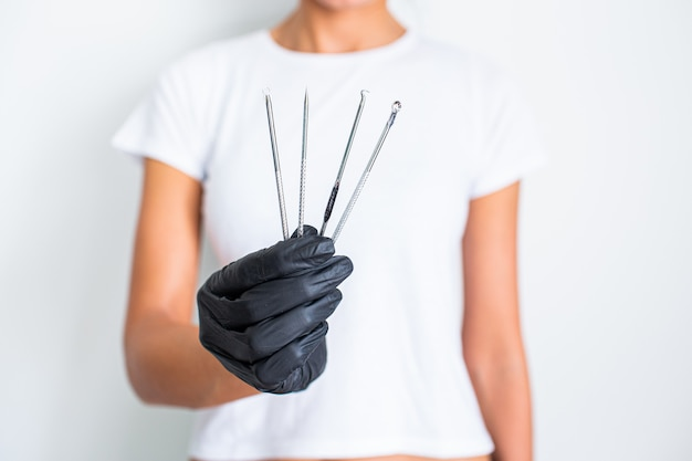 Tools for removing acne. tools of the cosmetologist for problem skin in woman's hand in black glove.