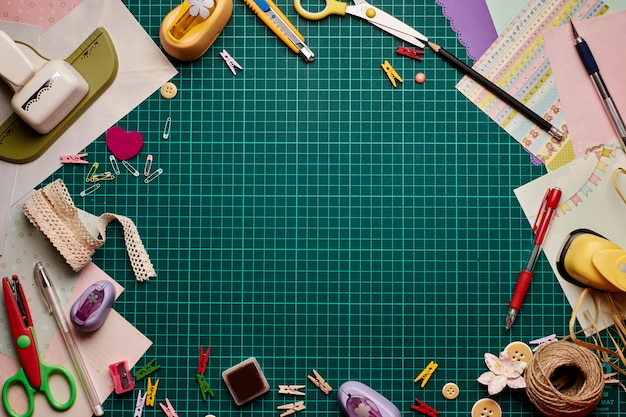 Tools for scrapbooking on the cutting mat. copy space in the middle.