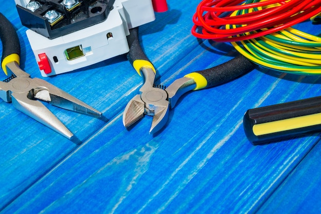Tools and spare parts for master electrician on blue wooden boards