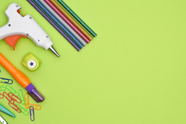 Tools and stationery items for creativity on green background. preschool and school handcraft education tools. top view of glue gun, creative punch, paperclips
