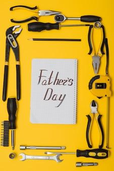 黄色の背景にツールの上面図。ツール付き父の日カード。ペンチ、オープンレンチ、ドライバー、ステープルガンをサークルに入れます。