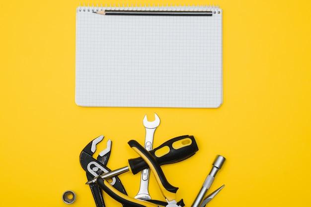 Вид сверху инструменты на желтом фоне. плоские плоскогубцы, гаечные ключи, отвертки и степлер с местом для копирования.