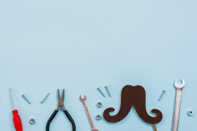Tools with black paper mustache on table