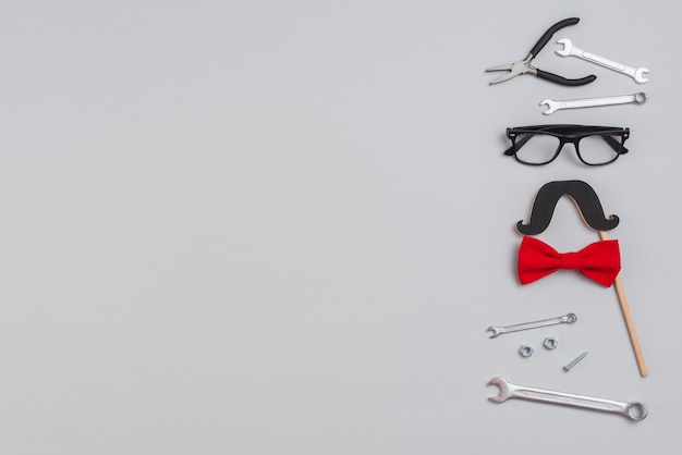 Tools with paper mustache, glasses and bow tie
