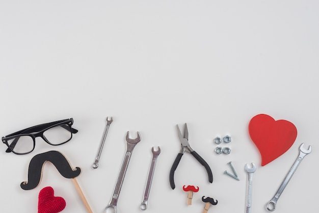 Tools with paper mustache, glasses and hearts