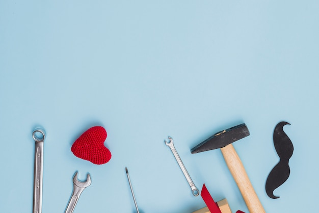 Tools with paper mustache and toy heart