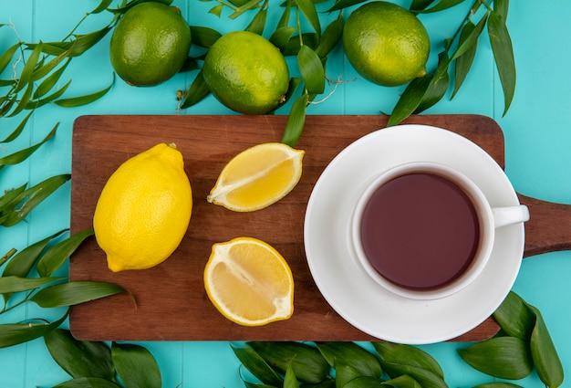 Vista superiore di limoni freschi verdi e gialli sul bordo della cucina in legno con una tazza di tè e foglie sul blu