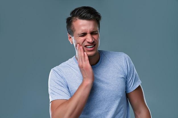 歯痛の概念。痛みを感じ、手で頬を持ち、ひどい歯痛に苦しんでいる、痛みを伴う表情でカメラを見ている若い男性の屋内ショット