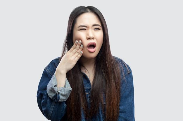 치통. 화장을 하고 고통스러운 치아를 들고 있는 캐주얼 블루 데님 재킷을 입은 아픈 아름다운 브루네트 아시아 젊은 여성의 초상화. 밝은 회색 배경에 격리된 실내 스튜디오 촬영.