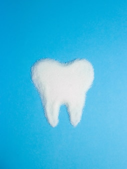 Tooth from sugar on blue , symbol
