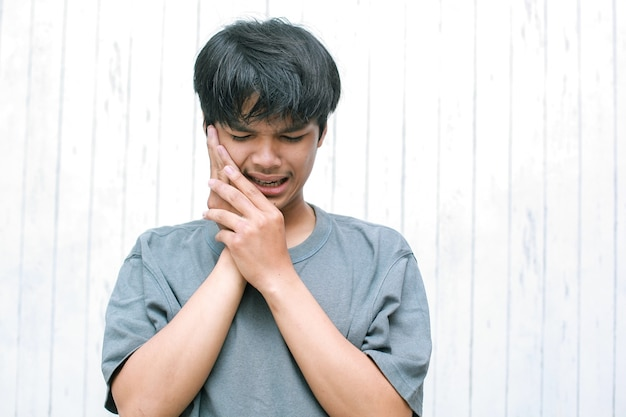 Tooth pain young man suffering from terrible strong teeth pain with touching cheek with hand