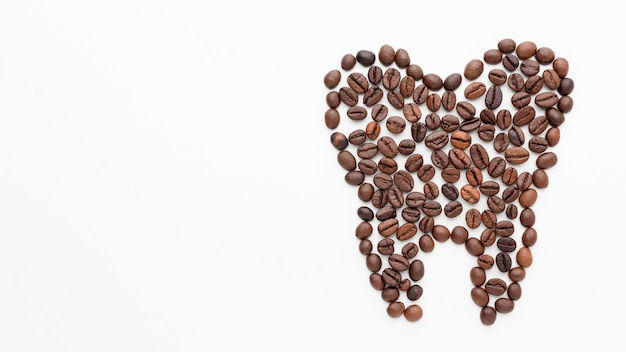 Tooth shape made of coffee beans with copy-space