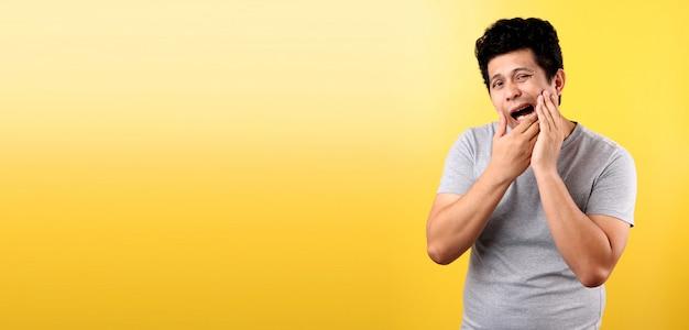 치통 개념. 젊은 아시아 남자 느낌 통증, 나쁜 치아 ache.on 노란색 벽에서 고통으로 손으로 그의 뺨을 잡고의 실내 샷.