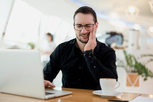 歯痛の概念。歯痛、虫歯または過敏症に苦しんでいる若いフリーランサーの男性。定期的に歯科医を訪ねてください!彼の頬を覆っている黒いシャツを着た男。現代のラップトップとテーブルの上のコーヒー。