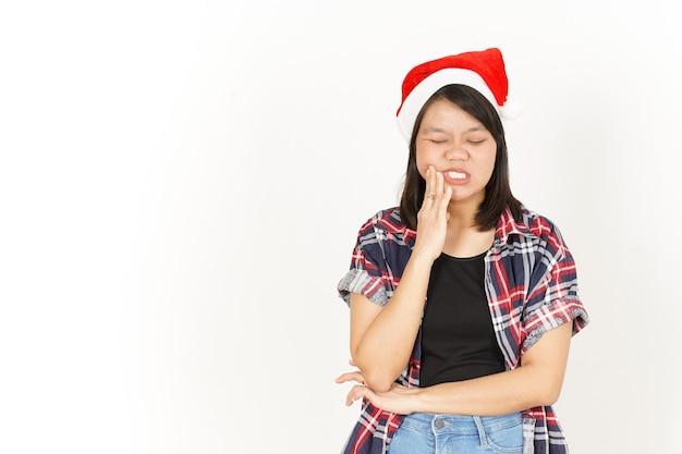 치통 제스처 흰색 절연 빨간 격자 무늬 셔츠와 산타 모자를 입고 아름 다운 아시아 여자