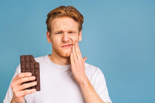 歯痛。歯痛に苦しんでいるハンサムな若い男、痛みを止めるために彼の頬に触れて