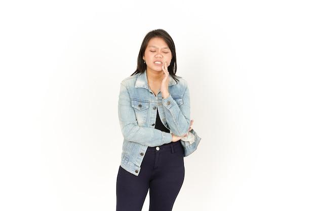 白い背景で隔離のジーンズジャケットと黒のシャツを着ている美しいアジアの女性の歯痛