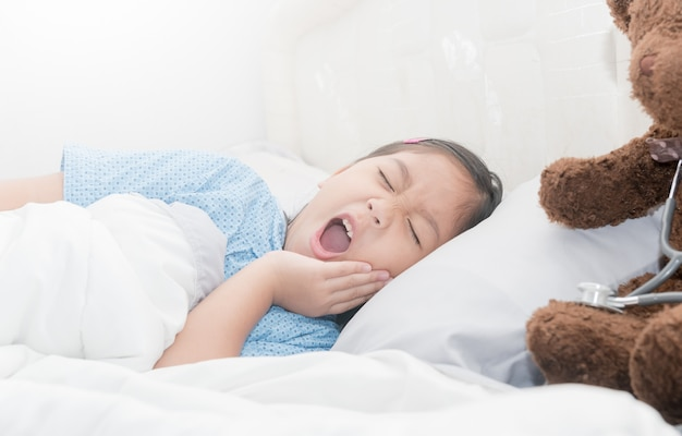 Toothache, sad little girl suffering from toothache on bed in bedroom, health care concept