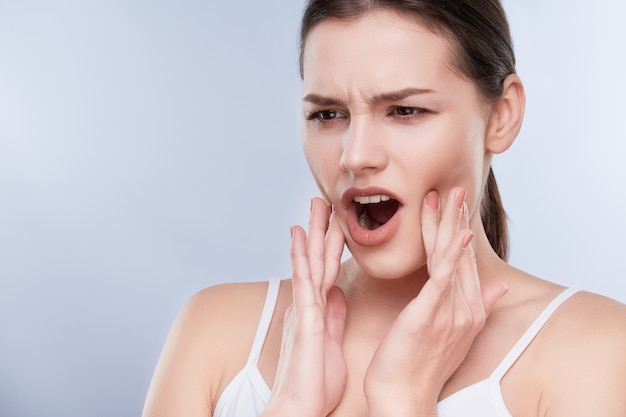Toothache, white teeth. head and shoulders of young woman suffering from toothache, teethcare problems. painful expression on face of woman, hands near face