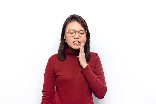 뺨에 손을 대고 치통을 입은 젊은 아름다운 아시아 여성의 빨간 셔츠
