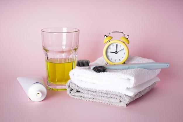 ピンクの目覚まし時計付き歯ブラシとタオル