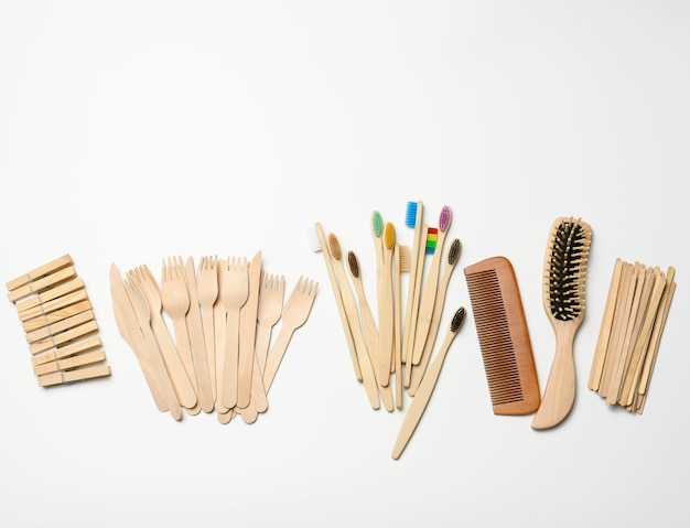 Toothbrush, comb, clothespin and other wooden items on a white background, top view, zero waste