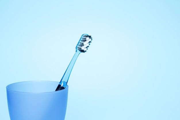 Toothbrush in a glass on blue background
