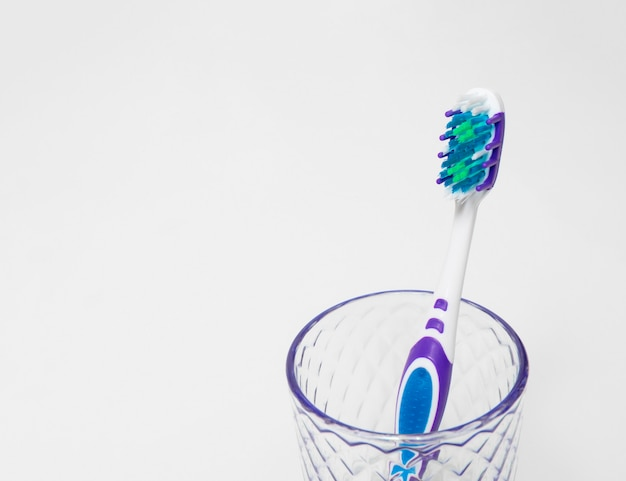 A toothbrush in a glass glass with room for text dental care and dentistry