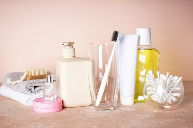 ガラスの歯ブラシとベージュの他のバスアメニティ