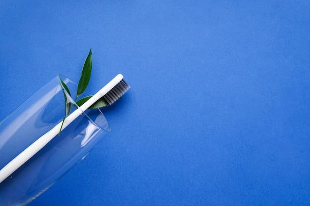 Зубная щетка в стакане на синем