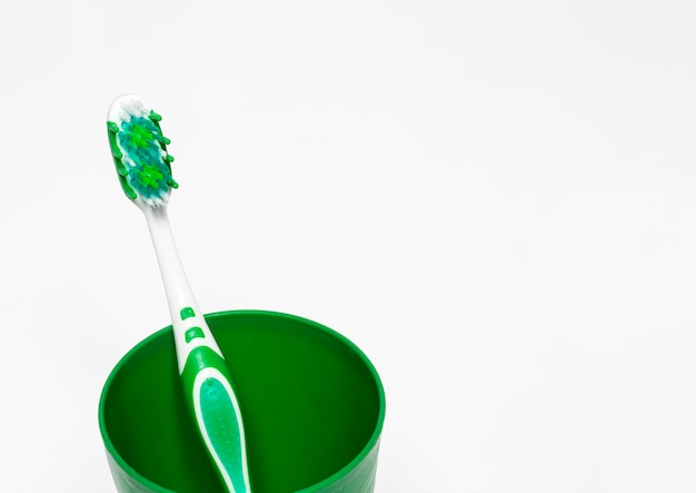 A toothbrush is green in a glass on a white with room for text, brushing your teeth and taking care of the mouth.