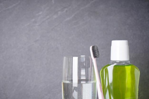 灰色の歯ブラシ、マウスウォッシュ、コップ一杯の水