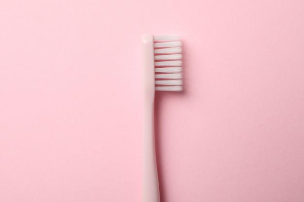 ピンクの表面に歯ブラシ。歯の手入れ